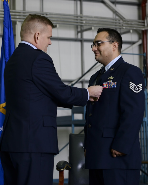 Col. Thomas D. Torkelson, the 100th Air Refueling Wing commander, presents Staff Sgt. Vicente Gomez, a 100th Aircraft Maintenance Squadron crew chief, with the Airman's Medal during a ceremony March 11, 2016, on Royal Air Force Mildenhall, England. Gomez received the honor for his courageous acts performed on May 12, 2014 by saving the lives of two victims from a potentially fatal car accident. (U.S. Air Force photo/Senior Airman Victoria H. Taylor)