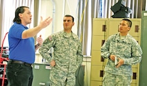 Brian Abel, tactical instructor, Communications Electronics Command, Field Support Branch, teaches Sgt. 1st Class Alexander Lopez and Cpl. Mitz Acasio, both with Headquarters and Headquarters Company, 1st Combat Aviation Brigade, 1st Infantry Division, how to operate SIPR and NIPR communications equipment Feb. 4 at Fort Riley.