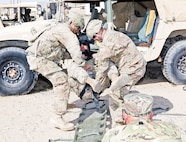 Sgt. Mathew Witte, bottom, casualty evacuation noncommissioned officer with Headquarters and Headquarters Company, 2nd Battalion, 70th Armor Regiment, 2nd Armored Brigade Combat Team, 1st Infantry Division, evaluates the extrication of a simulated casualty during Expert Field Medical Badge testing Feb. 3 at Camp Buehring, Kuwait. EFMB holder Witte was in charge of the third situational training exercise during EFMB testing Feb. 1 to 6.