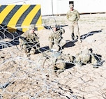 Staff Sgt. Clint Black, standing at center, is a senior battery ammunition chief with Battery B, 1st Battalion, 7th Field Artillery Regiment, 2nd Armored Brigade Combat Team, 1st Infantry Division. Here he evaluates candidates negotiating a wire obstacle during Expert Field Medical Badge training Jan. 30 at Camp Buehring, Kuwait.