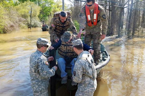 Soldiers help a man out of the bridge erection boat they used to check on residents who could not get out of their homes, in Ponchatoula, La., March 13, 2016. The Soldiers are assigned to the Louisiana National Guard's 2225th Multi-Role Bridge Company, 205th Engineer Battalion. The current of the river, which had overcome its banks and flooded the road, was too strong for regular boat motors to battle. (Louisiana National Guard photo/1st Lt. Rebekah Malone)
