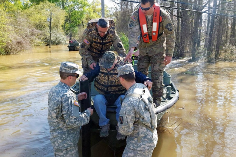 Soldiers help a flood victim from a rescue boat in Ponchatoula, La., March 13, 2016. The soldiers are assigned to the Louisiana National Guard's 2225th Multi-Role Bridge Company, 205th Engineer Battalion. Louisiana National Guard photo by 1st Lt. Rebekah Malone