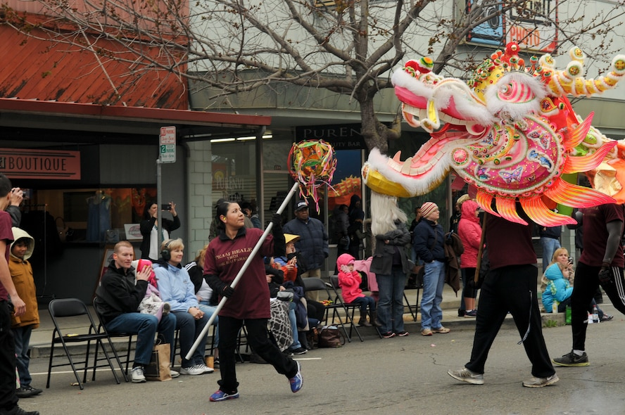 """2nd Lt. Nancy Gately leads The """"Hong Wan Lung"""" Dragon down the street in Marysville, California, Mar. 12, 2016. Beale Air Force Base volunteers brought the dragon to life for the Bok Kai parade. Beale has been a part of the parade for more than 20 years. The festival celebrates the Chinese Water God of the North."""