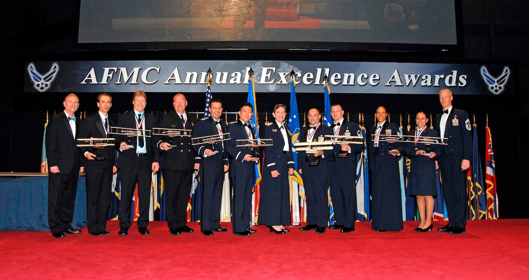 Air Force Materiel Command's 2015 Annual Excellence Award winners gather with AFMC leadership after the awards ceremony March 9, 2016. From left are Michael Gill, AFMC Executive Director; Andrew Mendoza; Eric Brickson; Steven Smith; Maj. David Jarnot; Capt. Jae Jeon; Gen. Ellen Pawlikowski, AFMC Commander; Master Sgt. Brian Partido; Master Sgt. Randy McKenzie; Technical Sgt. Kasmir Alford; Senior Airman Raquel Caramanno; and Chief Master Sgt. Michael Warner, AFMC Command Chief. (U.S. Air Force photo/Albert Bright)