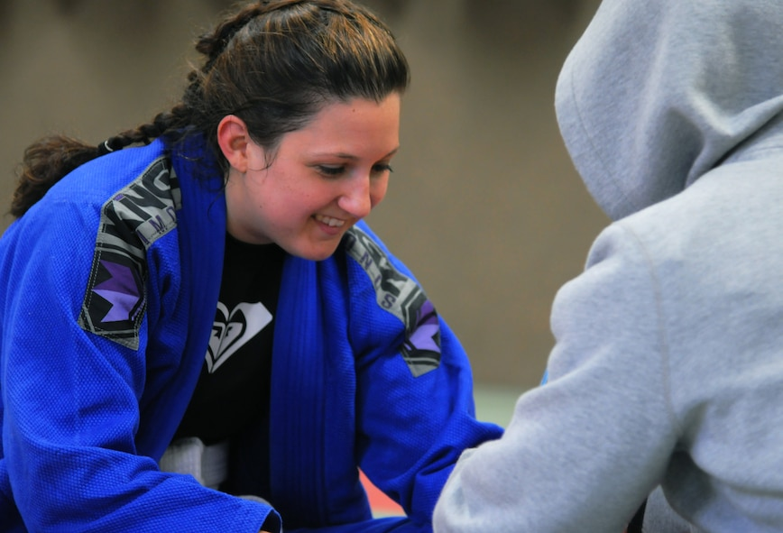 Mariah Johnson, a 52nd Force Support Squadron value-added tax officer and Spangdahlem Brazilian Jiu Jitsu class member, left, smiles while her coach wraps her hands before her first match at the Submissao competition in Karlsruhe, Germany, Feb. 20, 2016. Johnson lost seven pounds to make the weight class for her match and trained with fellow martial artists. (Courtesy photo)