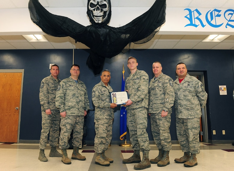 U.S. Air Force Airman 1st Class Austin King, an instrument and flight control systems journeyman assigned to the 509th Aircraft Maintenance Squadron, receives a Chief's Choice award at Whiteman Air Force Base, Mo., March 11, 2016. During the first ever, no-notice operational readiness exercise at Whiteman, King helped repair a landing gear conduit by replacing a 50-pin connector, which led to generating aircraft 11 hours under the standard time for Air Force Global Strike Command. During the past year, he also volunteered over 100 hours through opportunities like collecting 1,000 pounds of trash and debris through the Adopt-A-Highway program and coordinating three fundraising events as the dorm council president. (U.S. Air Force photo by Airman 1st Class Jazmin Smith)