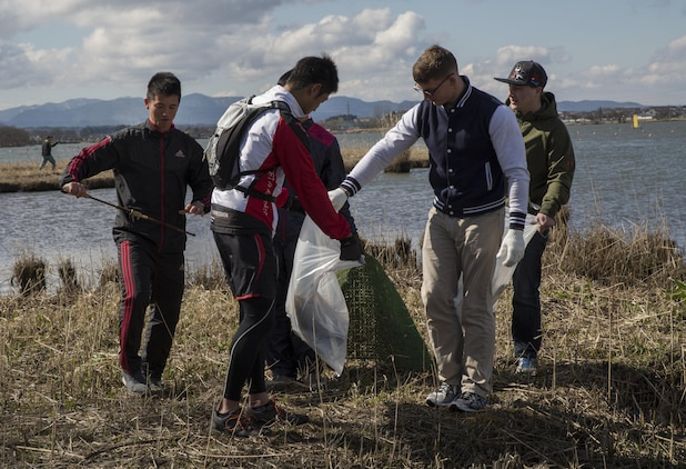 Members of Marine Fighter Attack Squadron (VMFA) 314, forward based at Marine Corps Air Station Iwakuni, Japan; Marine Aviation Logistics Squadron 12; Marine Aircraft Group 12 and Japan Air Self-Defense Force pick of trash during Operation Kibagata at Kibagata Park in Komatsu, Japan, March 12, 2016. Operation Kibagata brought the U.S. and Japan members participating in the Komatsu Aviation Training Relocation Exercise at Komatsu Air Base together to clean the park while providing the opportunity for the two services to socialize. (U.S. Marine Corps photo by Cpl. Nicole Zurbrugg/Released)