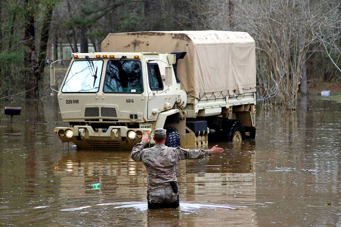 Army Sgt. David Breaud directs a high water vehicle down a flooded roadway at Latt Lake in Grant Parish, La., March 13, 2016. Breaud is assigned to the Louisiana National Guard's Headquarters Company, 225th Engineer Brigade. Army National Guard photo by Staff Sgt. Jerry Rushing