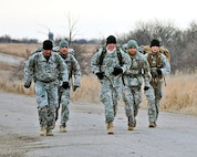 Five Soldiers from 1st Attack Reconnaissance Battalion, 1st Aviation Regiment, 1st Combat Aviation Brigade, 1st Infantry Division, ruck in the northern training area of Fort Riley Feb. 13 during their 21-mile training session for the Bataan Memorial Death March in New Mexico.