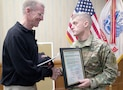 "Maj. Gen. Wayne W. Grigsby Jr., right, 1st Infantry Division and Fort Riley commanding general, presents retired Gen. Stanley A. McChrystal, left, former commander of U.S. and International Security Assistance Forces Afghanistan, with a certificate naming him an honorary lifetime member of the ""Big Red One"" March 3 during the leadership development program at Riley's Conference Center. McChrystal's father served as a battalion commander in the 1st Inf. Div. during the Vietnam War."