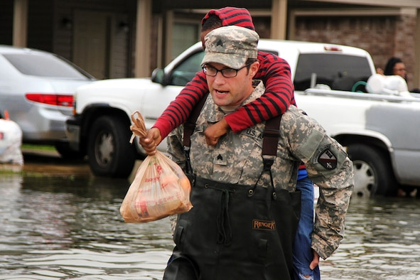 Sgt. Jason C. Carroll, an electronic warfare specialist with the Louisiana National Guard's 528th Engineer Battalion, 225th Engineer Brigade, carries a young resident through flooded streets in Monroe, La., March 10, 2016. The 528th EN BN used light medium tactical vehicles in cooperation with the Ouachita Parish Sheriff's Office to navigate through high waters in order to assist the residents who wished to leave. (U.S. Army National Guard photo/Spc. Tarell J. Bilbo)