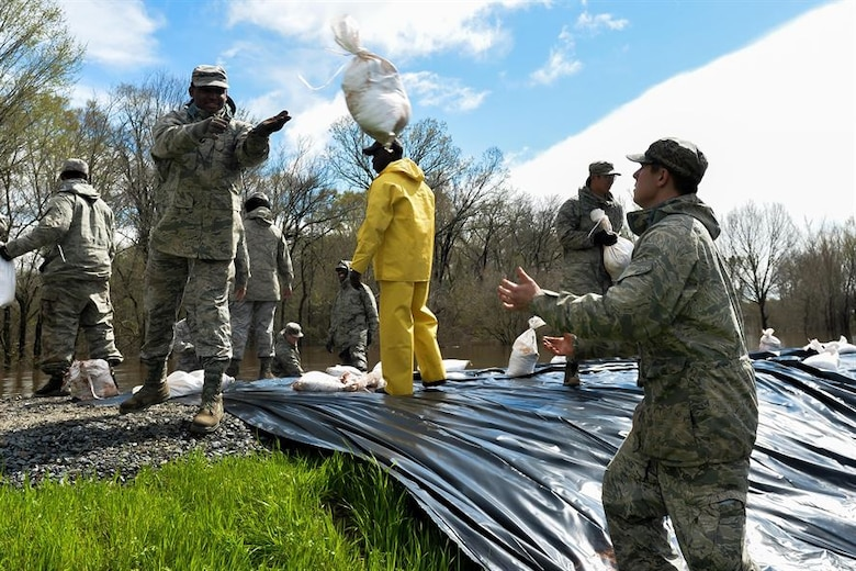An Airman throws a sandbag to his partner during the construction of protective flood barriers over the Red Chute Bayou levee in Bossier City, La., March 10, 2016. The Airmen are assigned to the 2nd Logistics Readiness Squadron. (Air Force photo/Senior Airman Mozer Da Cunha)