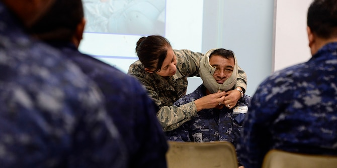 Maj. Helda Carey, 12th Air Force (Air Forces Southern) international health specialist, demonstrates techniques for wrapping a head wound during a U.S. Air Force and Salvadoran air force subject matter expert exchange at Ilopango Air Base, El Salvador, March 8, 2016. 12th Air Force (Air Forces Southern) surgeon general's office, led a five member team of medics from around the U.S. Air Force on a week-long medical subject matter expert exchange in El Salvador. (U.S. Air Force photo by Tech. Sgt. Heather R. Redman/Released)