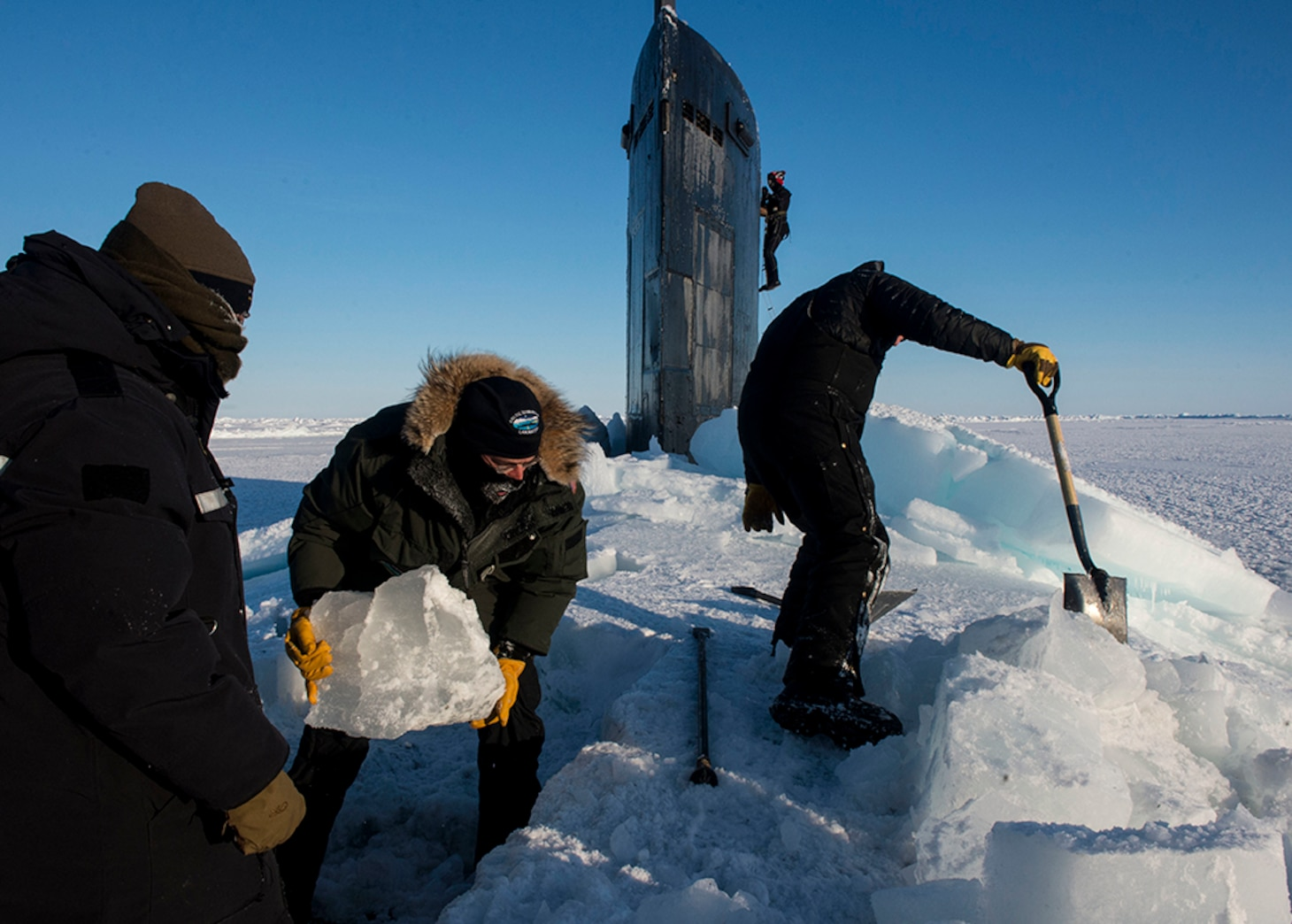 ARCTIC CIRCLE (March 14, 2016) Sailors and civilians, assigned to Arctic Submarine Lab, clear the ice from the hatch of USS Hampton (SSN 767) during Ice Exercise (ICEX) 2016. ICEX 2016 is a five-week exercise designed to research, test, and evaluate operational capabilities in the region. ICEX 2016 allows the U.S. Navy to assess operational readiness in the Arctic, increase experience in the region, advance understanding of the Arctic environment, and develop partnerships and collaborative efforts.