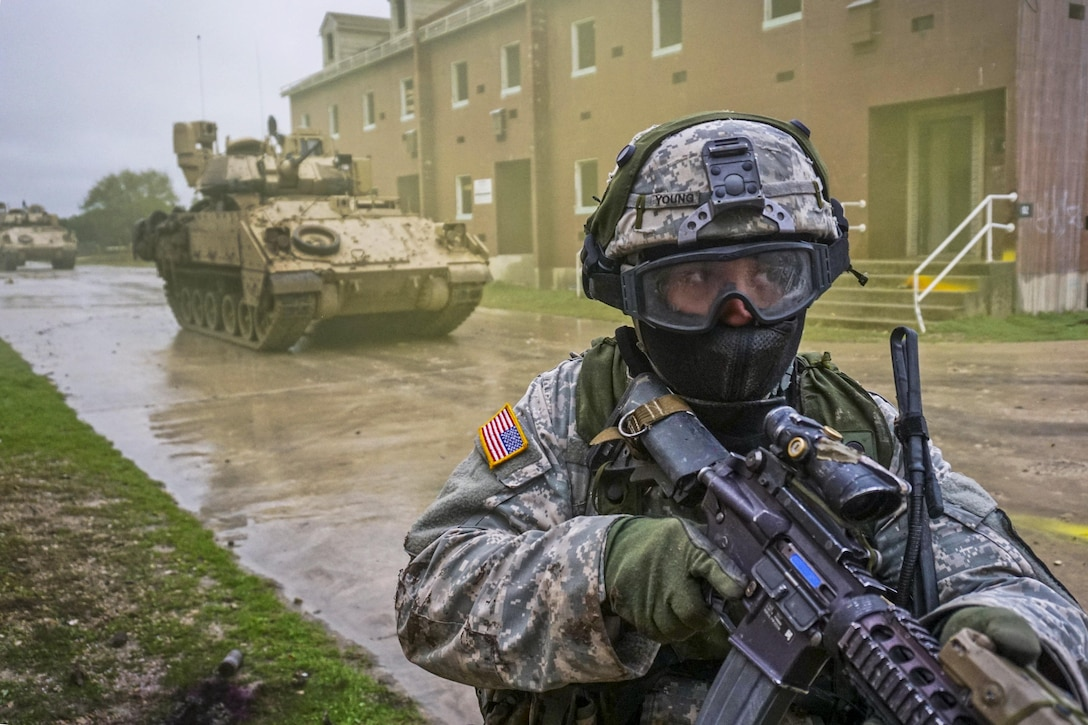 A soldier moves through an urban training facility and uses simulated rounds to enhance the training's realism on Fort Hood, Texas, March 10, 2016. The soldier is assigned to the 1st Cavalry Division's Company B, 2nd Battalion, 7th Cavalry Regiment, 3rd Armored Brigade Combat Team. Army photo by Sgt. Brandon Banzhaf