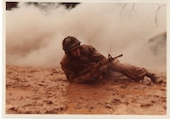 c. 1980. This Reserve Marine crawls through mud and smoke to advance on an enemy position during a training exercise.