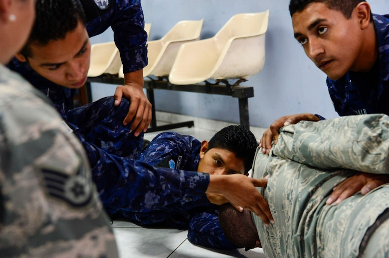 U.S. Air Force Staff Sgt. Karina Cortes and Senior Airman Jacob Radford, 628th Medical Operations Squadron medical technicians, take a group of Salvadoran air force members through self-aid buddy care exercises during a medical subject matter expert exchange at Ilopango Air Base, El Salvador, March 9, 2016. 12th Air Force (Air Forces Southern) surgeon general's office, led a five-member team of medics from around the U.S. Air Force on a week-long medical subject matter expert exchange in El Salvador. (U.S. Air Force photo by Tech. Sgt. Heather R. Redman/Released)