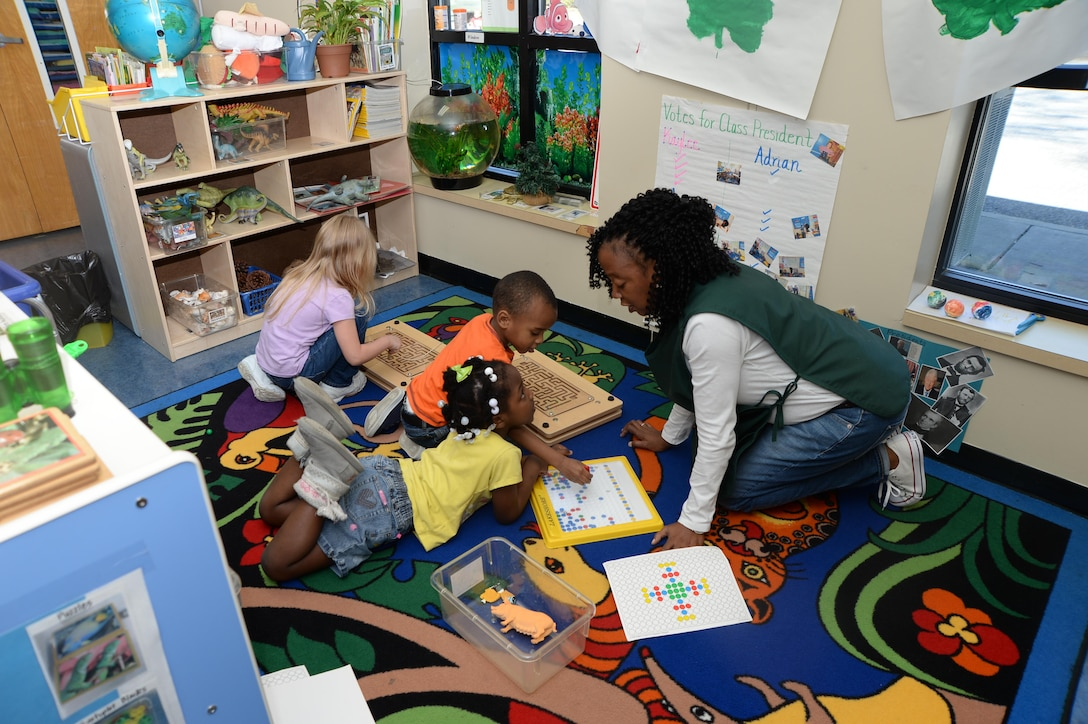 Pre-K students play a game at the Child Development Center while an employee asks what colors were on the board. The instructor was using entertainment to teach colors.