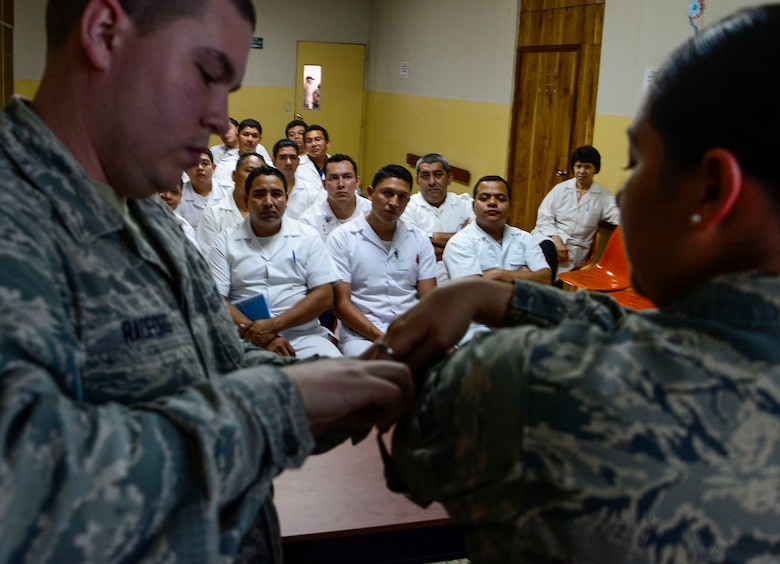 U.S. Air Force Senior Airman Jacob Radford and Staff Sgt. Karina Cortes, medical technicians stationed at Joint Base Charleston, S.C., demonstrate how to apply a tourniquet to medical technicians in training at Hospital Militar de El Salvador during a medical subject matter expert exchange in San Salvador, El Salvador, March 11, 2016. Earlier in the week, Carey led a team of Air Force medical professionals in a week-long exchange with Salvadoran medics at Ilopango Air Base.  After the subject matter expert exchange was completed, the team was invited to a share their expertise with members of the Hospital Militar de El Salvador.  (U.S. Air Force photo by Tech. Sgt. Heather R. Redman/Released)