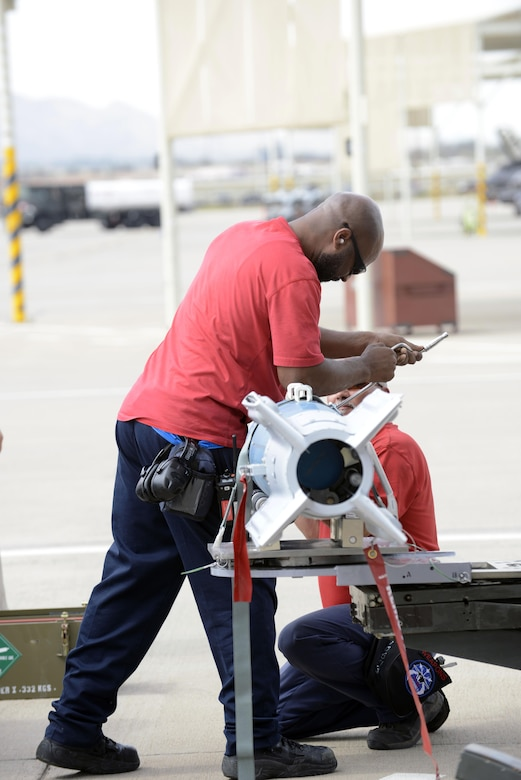 Weapons load crew members from the 62nd Aircraft Maintenance Unit prepare to load laser-guided bombs onto an F-35 Lightening II March 11, 2016, at Luke Air Force Base, Ariz. The F-35 Lightning II program took another step toward initial operational capability yesterday when two aircraft assigned to the 62nd Fighter Squadron successfully employed four laser guided bombs on the Barry M. Goldwater Range. The maintenance load crew team was comprised of Lockheed Martin contractors. (U.S. Air Force Photo by Senior Airman Devante Williams)