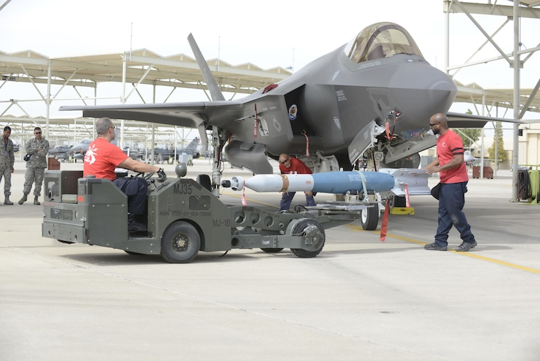 Weapons load crew members from the 62nd Aircraft Maintenance Unit load laser-guided bombs onto an F-35 Lightening II March 11, 2016 at Luke Air Force Base, Ariz. The F-35A Lightning II program took another step toward initial operational capability yesterday when two aircraft assigned to the 62nd Fighter Squadron successfully employed four laser guided bombs on the Barry M. Goldwater Range. The maintenance load crew team was comprised of Lockheed Martin contractors. (U.S. Air Force Photo by Senior Airman Devante Williams)