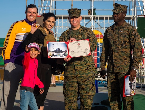 As part of the Yuma Patriot Festival, Telemundo's Fernanda Robles participates in the Marine Corps Battle Challenge and is awarded by station commanding officer Col. Ricardo Martinez and station Sgt. Maj. Delvin Smythe, at Marine Corps Air Station Yuma, Ariz., Saturday, Feb. 27, 2016.