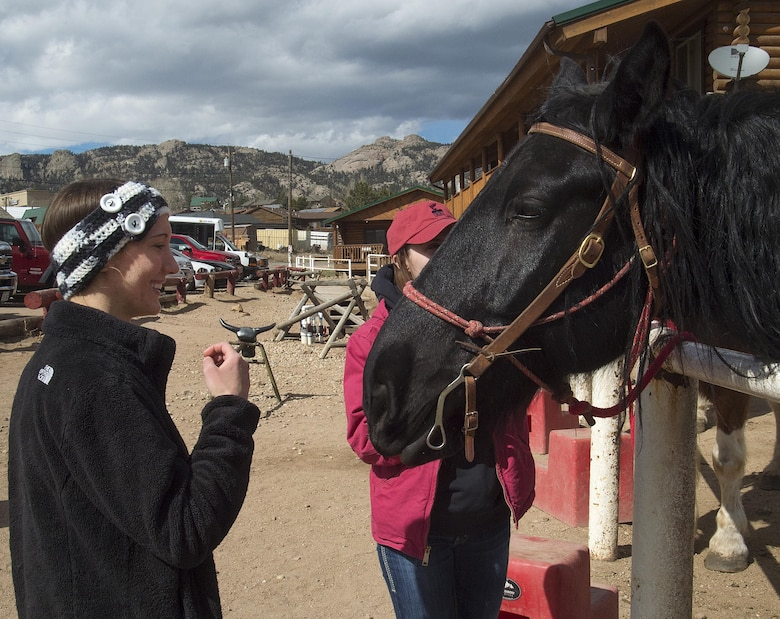 Brittany Lee and 1st Lt. Lindsey Byrd, 321st Missile Squadron, visit with Tracy the horse March 13, 2016, before the start of their trail ride in Estes Park, Colo. Lee and Byrd had made the trip down from F.E. Warren Air Force Base, Wyo., as part of a trip sponsored by the base's outdoor recreation office. (U.S. Air Force photo by R.J. Oriez)