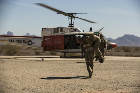 "Marines with Search and Rescue, based out of Marine Corps Air Station Yuma, Ariz., wait as a casualty is rushed to their HH-1N ""Huey"" helicopter during simulated medical and casualty evacuations in support of the Special Operations Terminal Air Control Course at Yuma Proving Ground, Friday, March 4, 2016."