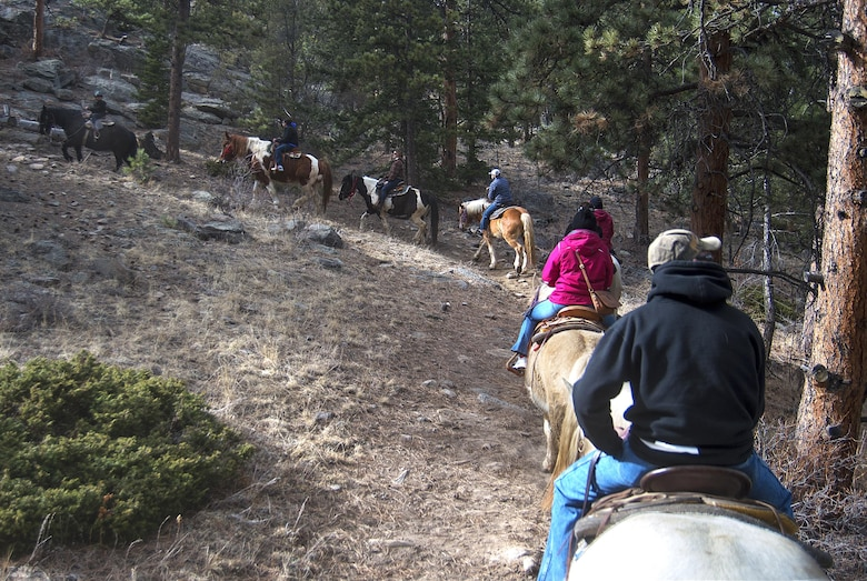 A line of Airmen, retirees and dependents from F.E. Warren Air Force Base, Wyo., thread their mounts along a trail in the Arapaho-Roosevelt National Forest near Estes Park, Colo., March 13, 2016. A group of ten came down to horseback ride as part of a trip set up by the base's Outdoor Recreation office. (U.S. Air Force Photo by R.J. Oriez)
