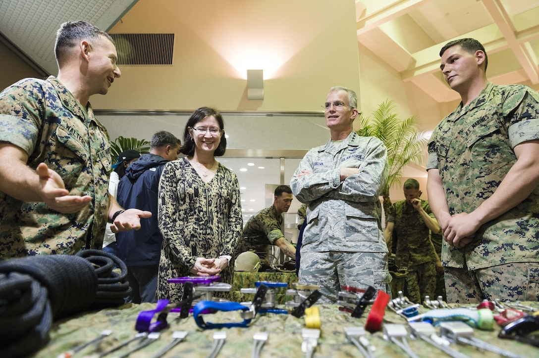 """Air Force Gen. Paul J. Selva, center right, vice chairman of the Joint Chiefs of Staff, and his wife, Deanie, center left, receive a static equipment briefing by a Marine Corps staff sergeant during a USO spring entertainment tour stop on Camp Hansen, Japan, March 13, 2016. Selva is leading the USO spring tour, which features Miss America 2016 Betty Cantrell; country music artist and Army veteran Craig Morgan; pro football player Charles Tillman; and UFC fighters Anthony Pettis and Donald """"Cowboy"""" Cerrone. DoD photo by Army Staff Sgt. Sean K. Harp"""
