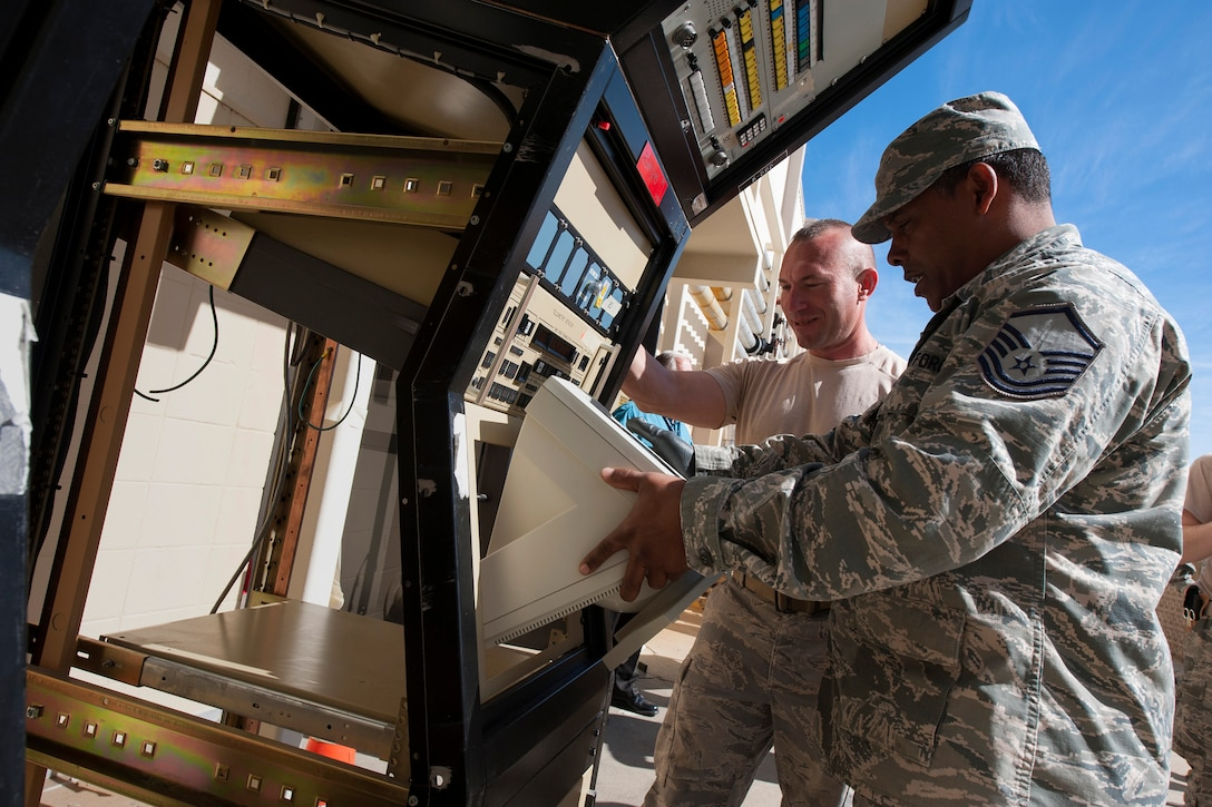 Master Sgt. Maurice McKenniss, 270th Engineering Installation Squadron, Range Simulation Center Installer, and TSgt Mark Yurkiewicz, 270th EIS, Telemetry Analog Equipment Room Installer, disassemble a legacy console unit from the Launch and Test Range System prior to its relocation to Vandenberg's Space and Missile Heritage Center March 2, 2016, Vandenberg Air Force Base, Calif. McKenniss and Yurkiewicz are part of an Air National Guard EI team working on a relocation of the Launch and Test Range System for the Western Range. (U.S. Air Force photo by Michael Peterson/released)