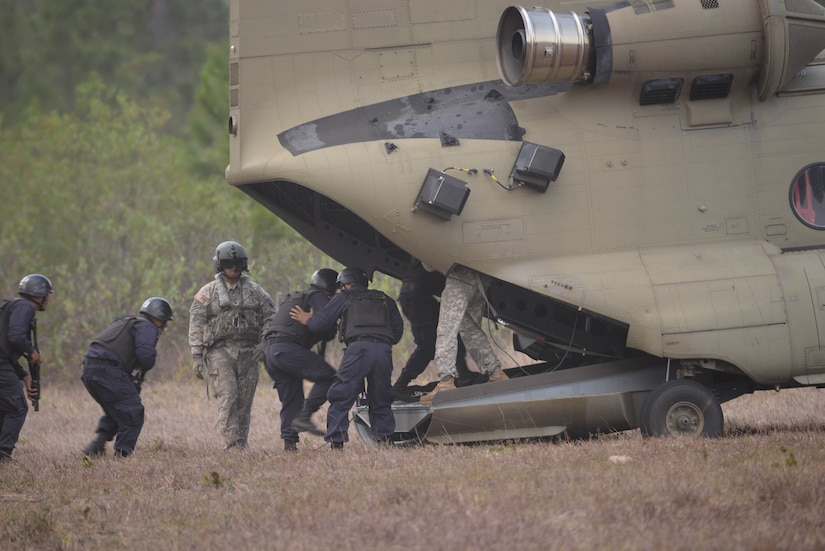 U.S. Army Sgt. Jesse Gomez, 1-228 Aviation Battalion crew chief, directs Honduran response forces as they board a U.S. Army CH-47 Chinook helicopter Feb. 26, 2016, near Soto Cano Air Base, Honduras, prior to a personnel recovery exercise. U.S and Honduran forces regularly train together to build their knowledge of techniques and capabilities in case they would ever need to operate together in real-world personnel recovery scenario. (U.S. Air Force photo by Staff Sgt. Westin Warburton/Released)