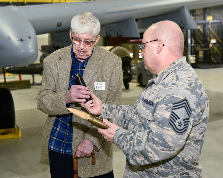 Chief Master Sgt. David Myers of the 127th Aircraft Maintenance Squadron shows a dummy 30mm round to Philas Kelly, who, at age 102, is likely the oldest living member of the 107th Observation Squadron of the Michigan National Guard. Myers and his team of maintenance Airmen support the current 107th Fighter Squadron, which flies the A-10 Thunderbolt II aircraft. Kelly visited his old unit at Selfridge Air National Guard Base, Mich., on March 15, 2016. (U.S. Air National Guard photo by Terry Atwell)