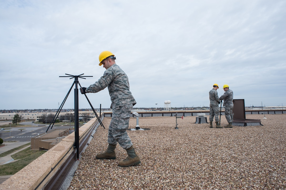 Senior Airman David Hopper, a cable and antenna technician with the 205th Engineering Installation Squadron from Will Rogers Air National Guard Base in Oklahoma City, moves a UVU-200 dual-band base station antenna to its position near a roof's ledge, March 6, 2016, at Tinker Air Force Base in Oklahoma City. Hopper was a part of one of the two teams from the 205 EIS guard unit that worked to setup and repair antennas for active-duty squadrons at Tinker AFB.