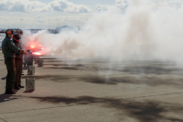 Japan Maritime Self-Defense Force aviators ignite nighttime smoke signals during Winter Survival Training at Marine Corps Air Station Iwakuni, Japan, March 9-11, 2016. Mandatory for all aviators and aircrew, the JMSDF conducts this training semi-annually, once in the summer and once in the winter. The aviators set off two smoke signals: red smoke for daytime and gray smoke with a red flashing light for nighttime. (U.S. Marine Corps photo by Lance Cpl. Aaron Henson/Released)