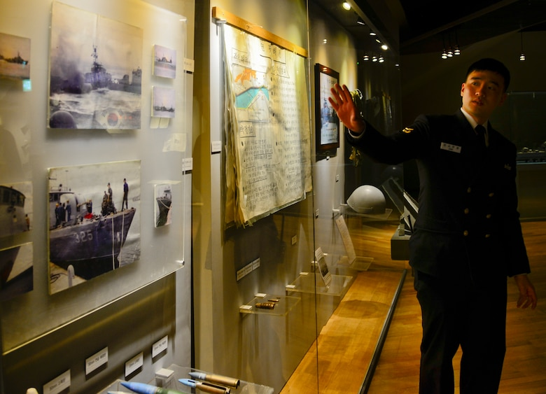 Republic of Korea Navy Petty Officer 1st Class Jung, Samuel, shows photos from the Yeonpyeong Sea Battles in the West Sea Protection Hall at the ROK Navy 2nd Fleet Command in Pyeongtaek-si, Gyeonggi-do Province, on Feb. 26, 2016. The sea battles took place June 15, 1999, and June 29, 2002, and are two of recent attacks on South Korea from North Korea patrols. (U.S. Air Force photo by Senior Airman Kristin High/Released)