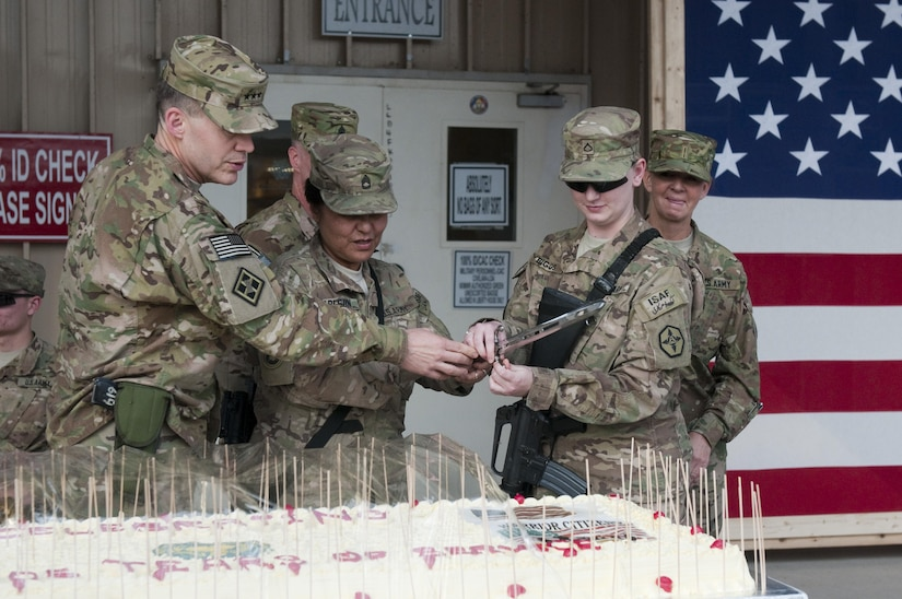 Sgt. 1st Class Sagrario Carlson, 311th Expeditionary Sustainment Command, the oldest Army Reserve soldier and Spc. Megan Biggs, 652nd Regional Support Group, the youngest Army Reserve soldier stationed at Kandahar Airfield, cut the 105th Army Reserve birthday cake with Lt. Gen. Jeffrey W. Talley, commander of the Army Reserve, April 26 during a ceremony. (U.S. Army photo by Sgt. Phillip Valentine, 311th Expeditionary Sustainment Command Public Affairs)