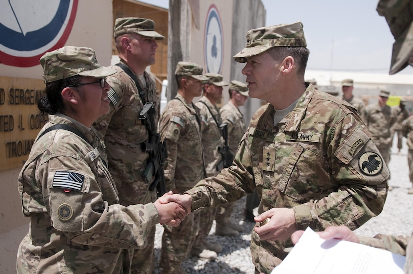 U.S. Army Lt. Gen. Jeffrey Talley, right, the chief of the Army Reserve, presents a challenge coin to Spc. Raquel Luis during an awards ceremony at Kandahar Airfield in Kandahar province, Afghanistan, April 27, 2013. Luis was assigned to the 311th Sustainment Command. (U.S. Army photo by Sgt. Phillip Valentine/Released)
