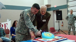 Iowa Army Reserve soldier Spc. Joseph Davison, most junior soldier assigned to 1st battalion, 383rd Training Support Battalion, 166th Aviation Brigade, First Army Division West – based at Fort Des Moines, cuts a birthday cake with Mayor Pro Tem T.H. Bob Mahaffey during the 106th birthday celebration of the Army Reserve on April 5. The honor of the most senior enlisted to cut the cake with the most junior soldier was extended to Mahaffey. (Photo by Capt. Mark Butcher)