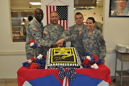 Reserve Soldiers celebrate the 107th birthday of the Reserve April 23 at the Maj. Chester Garret Dining Facility on McGregor Range, N.M. From Left to right: Lt. Col. Bradford M. Shaw, commander of 2206th Mobilization Support Battalion, Master Sgt. Lorenzo Sifuentes, special projects noncommissioned officer in charge, Spc. Brandon Lievense, chaplain's assistant, Command Sgt. Maj. Jane P. Baldwin, command sergeant major, 2206th MSB, during the ceremonial cutting of the cake.