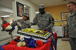 Command Sgt. Maj. Jane P. Baldwin, command sergeant major, 2206th Mobilization Support Battalion, left, and Lt. Col. Bradford Shaw, commander, 2206th MSB, center, cuts the birthday cake celebrating 107 years of the U.S. Army Reserve, April 23, at the Maj. Chester Garret Dining Facility on McGregor Range, N.M. Far right, Spc. Brandon Lievense, chaplain's assistant, looks on before distributing pieces of cake during the lunch service.