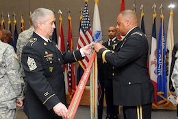 Command Sgt. Maj. Kevin Greene, command sergeant major, 85th Support Command; left, and Brig. Gen. Gracus K. Dunn, commanding general, 85th Support Command and deputy commanding general for support, First Army Division-West; add the Army Superior Unit Award streamer to the unit's colors during a formal ceremony at the unit's headquarters during an Army Reserve birthday celebration on April 5. The Army Reserve's birthday is on April 23.