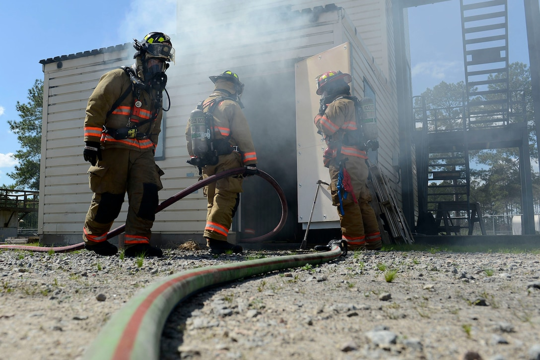 U.S. Airmen assigned to the 20th Civil Engineer Squadron fire department prepare to clear smoke from a training burn house at Shaw Air Force Base, S.C., March 14, 2016. Airmen assigned to the 20th CES utilize the burn house to practice procedures for extracting victims in a building fire scenario. (U.S. Air Force photo by Airman 1st Class Christopher Maldonado)
