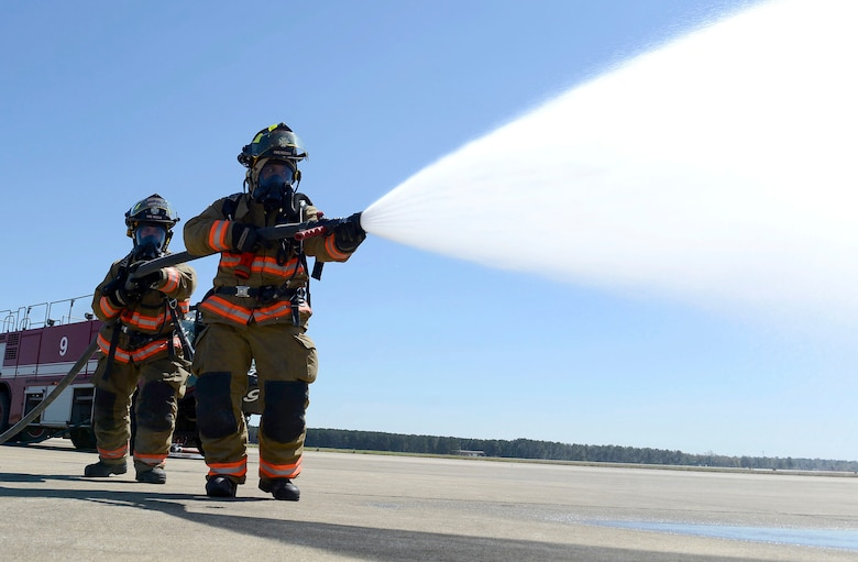 U.S. Air Force Senior Airman Joan Ortega, 20th Civil Engineer Squadron firefighter and Airman 1st Class John Derboghossian, 20th CES firefighter apprentice, use an inch and three quarter attack line hose while training on the flightline at Shaw Air Force Base, March 15, 2016. The fire hose has the power to shoot over 100 pounds of water per minute and helps in the rapid clearing of fire on buildings, vehicles and aircrafts. (U.S. Air Force photo by Airman 1st Class Christopher Maldonado)