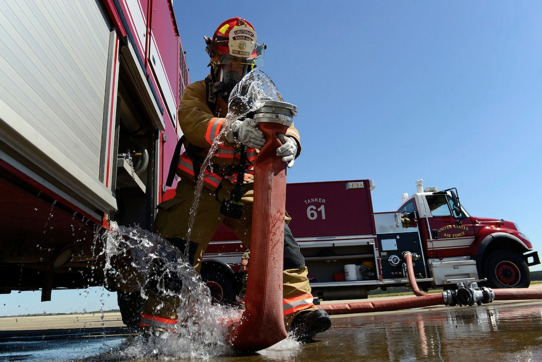 U.S. Air Force Staff Sgt. Larry Diaz, 20th Civil Engineer Squadron fire protection craftsman, removes a hose from a vehicle being supplied water from Tanker 61 during pilot ejection training at Shaw Air Force Base, S.C., March 15, 2016. Upon completion of training, hoses were disconnected and rolled back into their proper vehicles. (U.S. Air Force photo by Airman 1st Class Christopher Maldonado)