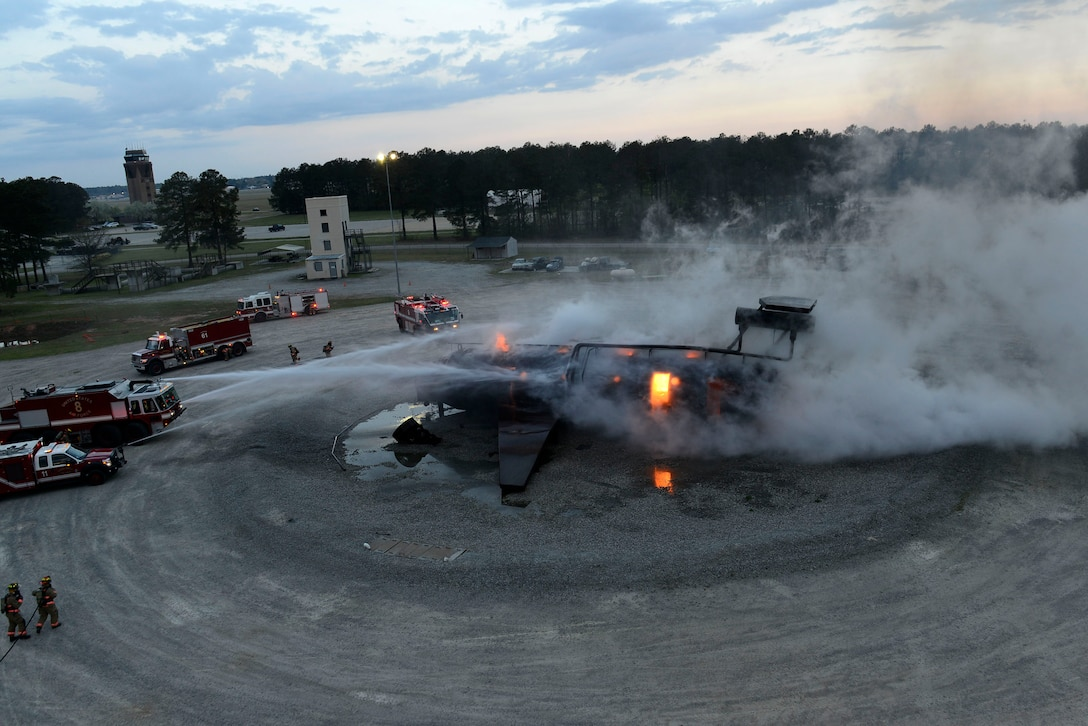 U.S. Airmen assigned to the 20th Civil Engineer Squadron fire department extinguish an aircraft fire during training at Shaw Air Force Base, S.C., March 17, 2016. Firefighters assigned to the 20th CES fire department train on a mock C-130 to test their response time and efficiency in extinguishing an aircraft fire. (U.S. Air Force photo by Airman 1st Class Christopher Maldonado)