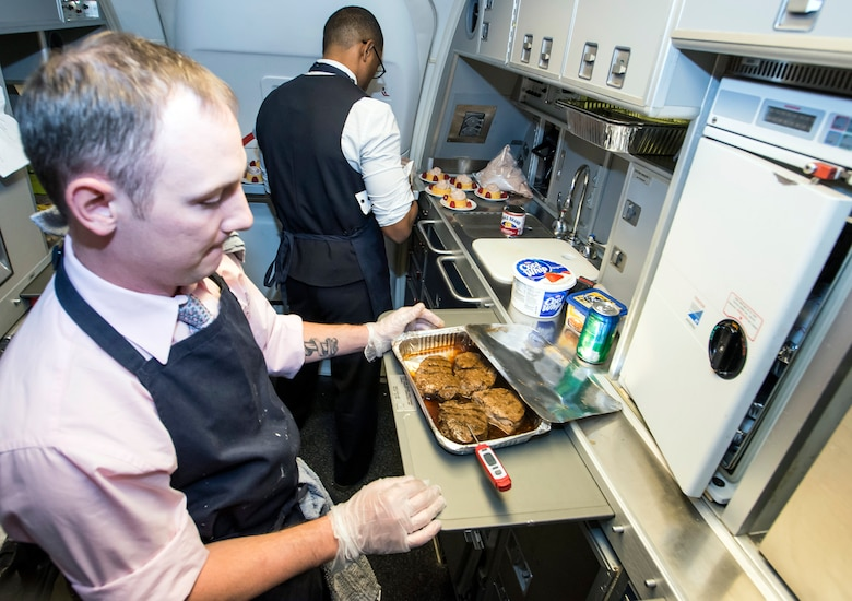 Tech. Sgt. Albert Meriano III and Staff Sgt. Casey Watson, 1st Airlift Squadron flight attendants, prepare lunch at about 50,000 feet while in flight to Royal Air Force Mildenhall, England, Oct. 10, 2015. While a flight attendant's primary duties is the safety of passengers, they are also culinary artists and experts with customs regulations. (U.S. Air Force photo/Senior Master Sgt. Kevin Wallace)