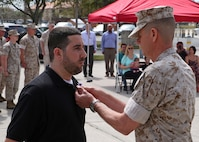 TAMPA, Fla. – Corporal Brian P. Johnson is presented the Purple Heart medal by Lieutenant. Gen. William D. Beydler Mar. 17, 2016, at a ceremony MacDill Air Force Base, Fla. Johnson received the Purple Heart for injuries he sustained on 26 July 2006, during combat operations with Combined Regimental Combat Team 5, in Fallujah, Iraq. Johnson completed his active service in November of 2006. Beydler is the Commanding General of Marine Corps Forces Central Command.