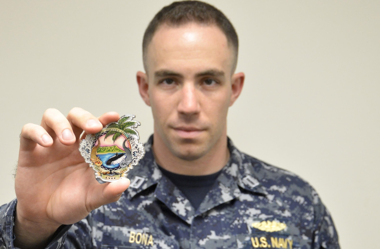 Lieutenant Nick Bona presents the 116th Pacific Fleet Submarine Force birthday ball's challenge coin. The ball celebrates 116 years of distinguished service by the submarine force. (U.S. Navy photo by Lieutenant Junior Grade Samuel Boyle/Released)