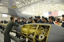 Technical Sgt. Erica Knight, 756th Air Refueling Squadron boom operator, showcases 459th Air Refueling Wing missions to a squadron of Royal Canadian Air Cadets inside a hangar on the Joint Base Andrews, Md., flight line March 15, 2016. The tour group observed the inner workings of a KC-135R Stratotanker engine, boom arm and cargo area as well as discussed life as a U.S. Air Force Reserve member with citizen Airmen. (U.S. Air Force photo/Staff Sgt. Kat Justen)